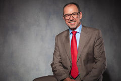 Bald businessman wearing glasses while posing. Elegant mature bald businessman wearing glasses while posing smiling seated in studio background Stock Images