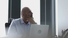 Bald businessman working at his laptop in his home office