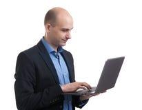 Bald businessman working on his laptop Royalty Free Stock Photos