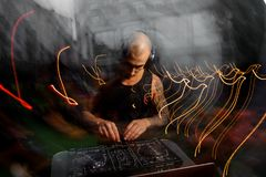 Bald club DJ with headphones mixes music. Young bald club DJ with headphones and tattoo, dressed in a black shirt mixes music Stock Images