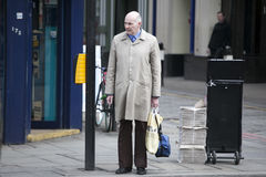 A bald, elderly man in a gray cloak stands at a traffic light, waiting to cross the street Royalty Free Stock Images