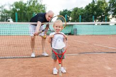 Portrait of the bald father and little daughter on the tennis court. Royalty Free Stock Image