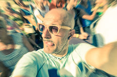 Bald funny man taking a selfie in the crowd with tongue out stock image