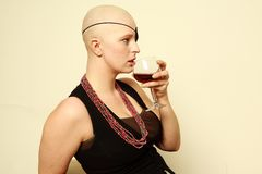 Bald girl with eye patch drinking wine Stock Images