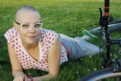 Bald girl with glasses. Bald woman lying on the grass  with bicycle Stock Photography