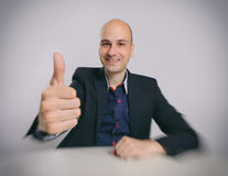 Bald guy sits at the desk Stock Images
