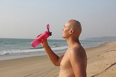 A bald, handsome man with a bare or bare torso is drinking water from a pink fitness bottle. The man is thirsty. Heat and thirst. India, Goa stock photo