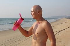 A bald, handsome man with a bare or bare torso is drinking water from a pink fitness bottle. The man is thirsty. Heat and thirst. India, Goa stock photos