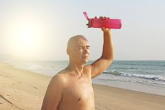A bald, handsome man with a naked or bare torso watering himself. With water from a pink fitness bottle. The man is thirsty. Heat and thirst. India, Goa royalty free stock photos
