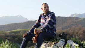 A bald, handsome man in nature eats a bread at beautiful mountain landscape. stock video