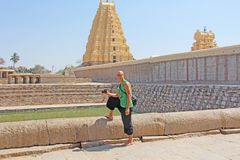 A bald and handsome tourist man wearing glasses, against the background of the Virupaksha temple, with a camera in his hands. The. Man is a photographer royalty free stock photography