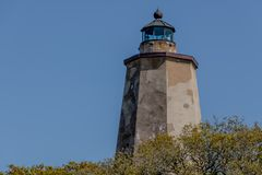 Bald Head Island Lighthouse in daylight. BALD HEAD ISLAND, NC - APRIL 14: Bald Head Lighthouse, known as Old Baldy, stands on Bald Head Island, NC on April 14 stock image