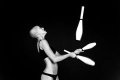 Bald-headed girl juggles. On black background Stock Images