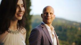 Bald-headed man admires his woman walking around the backyard stock footage