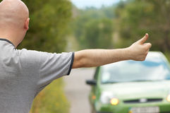 Bald-headed man hitching on road Royalty Free Stock Image