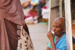 Bald hindu widow. Bald sad hindu widow drinking a tea on the street in Madurai Royalty Free Stock Photography