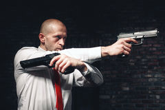 Bald hired killer in red tie aims a pistols Stock Images