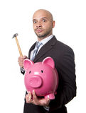 Bald Hispanic businessman with hammer in his hand holding pink piggybank ready to break the piggy bank and take money out Royalty Free Stock Photos
