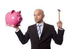 Bald Hispanic businessman with hammer in his hand holding pink piggybank ready to break the piggy bank and take money out Stock Photography