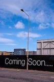 Bald kommen Anschlagtafel auf einer Stadtstraße lizenzfreies stockbild