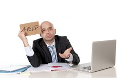 Bald latin business man over worked holding a help sign Royalty Free Stock Photography