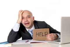 Bald latin business man over worked holding a help sign Royalty Free Stock Photo