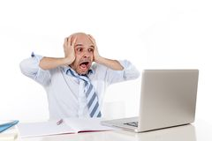 Bald latin businessman screaming at his latop Stock Photo