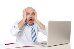 Bald latin businessman screaming at his latop Royalty Free Stock Photography