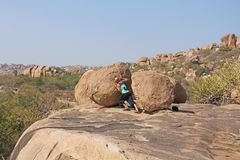Bald Male tourist and photographer in Hampi pushes a large stone. Large stones Hampi on the side of the village of Anegundi and Virupapur Gaddi. Large stones royalty free stock photos