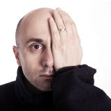 Bald man. With hand over his eye on white background Stock Photo