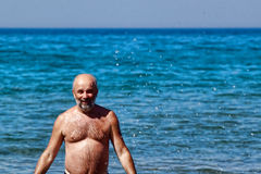 Bald man with a beard emerging from the sea Royalty Free Stock Image