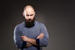 Bald man with a beard holding a pair of scissors. crossed hands Royalty Free Stock Photos