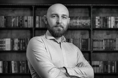 A bald man with a beard in the library. NBusinessman.nBlack and white photography Royalty Free Stock Image
