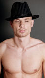 Bald man in black hat. Studio portrait of young bald muscular man with black hat Stock Image