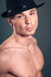 Bald man in black hat. Studio portrait of young bald muscular man with black hat Royalty Free Stock Images