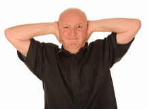Bald man covering ears Stock Images