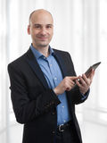 Bald man with digital tablet Stock Image