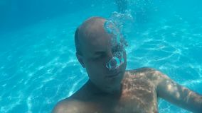 Bald man diving underwater swimming pool and blowing air bubble. Underwater view man blowing air bubble in transparent. Blue water pool in resort stock video footage