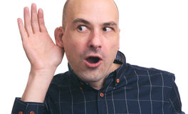 Bald man eavesdrops some news. Isolated on white stock image