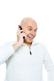 Bald man emotionally communicates by phone. Isolated. Studio Royalty Free Stock Image