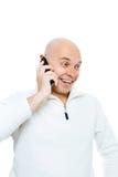 Bald man emotionally communicates by phone. Isolated. Studio Royalty Free Stock Image