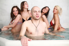 A bald man with four beautiful girls in swimsuits. A bald men with four beautiful girls in swimsuits at the pool royalty free stock photos