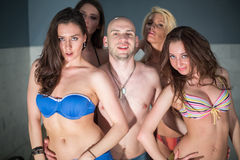 A bald man and four girls. A bald men and four beautiful girls in swimsuits stock photography