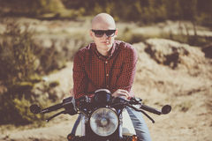Bald man with glasses sitting on an old vintage custom bike Stock Images