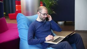 Bald man with glasses working on laptop with phone stock footage