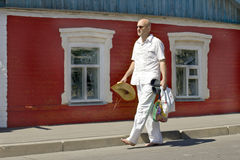 Bald man goes barefoot on the street Royalty Free Stock Photos