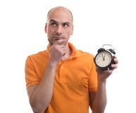 Bald man holding an alarm clock and thinking Stock Image