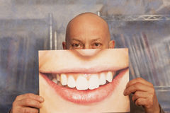 Bald man holding a card with a big smile Royalty Free Stock Photography