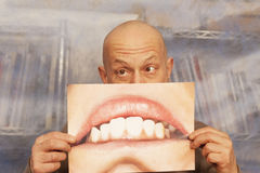 Bald man holding a card with a big smile Royalty Free Stock Image
