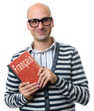 Bald man holds a textbook. Learning French concept. Bald man holds a textbook or dictionary. Learning French concept Stock Photos